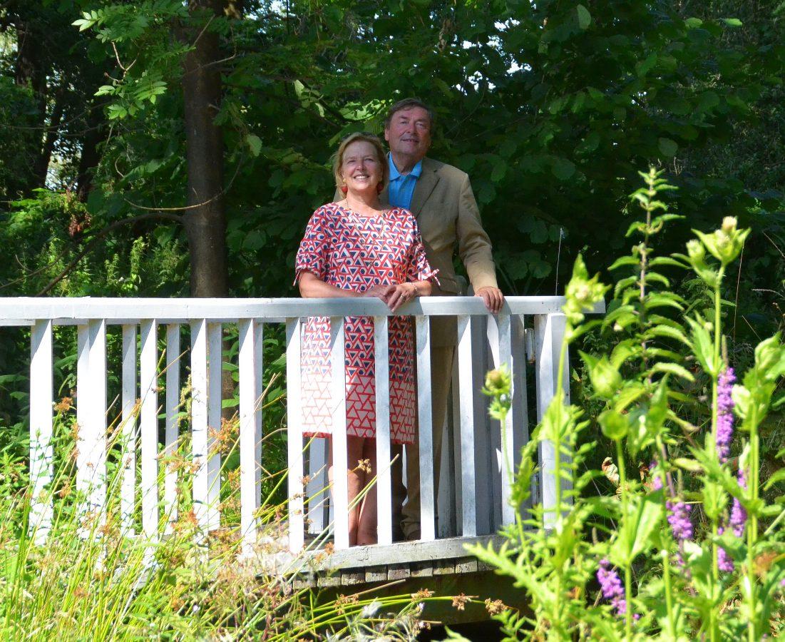 Anna und Nikolaus von Veltheim stehen auf einer kleinen Brücke im Garten, die zu einer Art Insel führt. Diese ist aber noch zugewachsen. Foto: Kjell Sonnemann